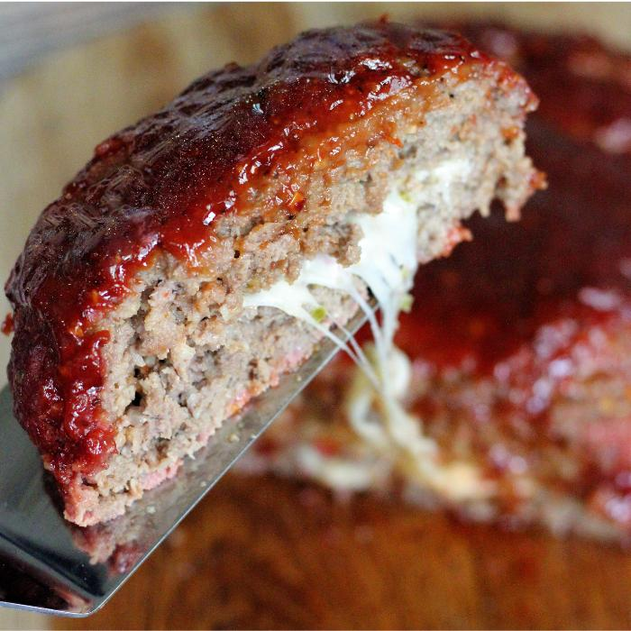 A slice of Jack'd up smoked meatloaf on a metal spatula with the remaining meatloaf in the background.