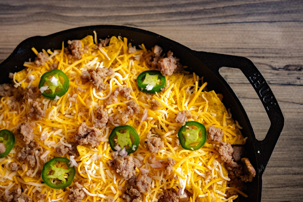 Shredded cheese, jalapenos, sliced jalapenos over eggs and tortilla chips in a casts iron skillet.