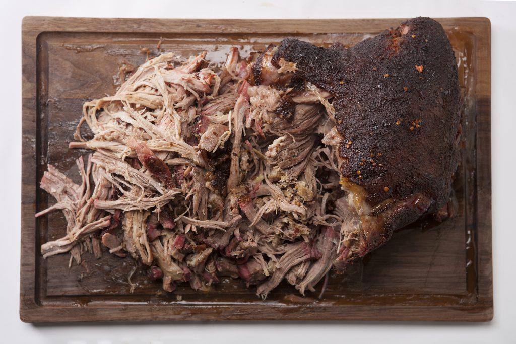shredded brown sugar pulled pork on a wooden cutting board.