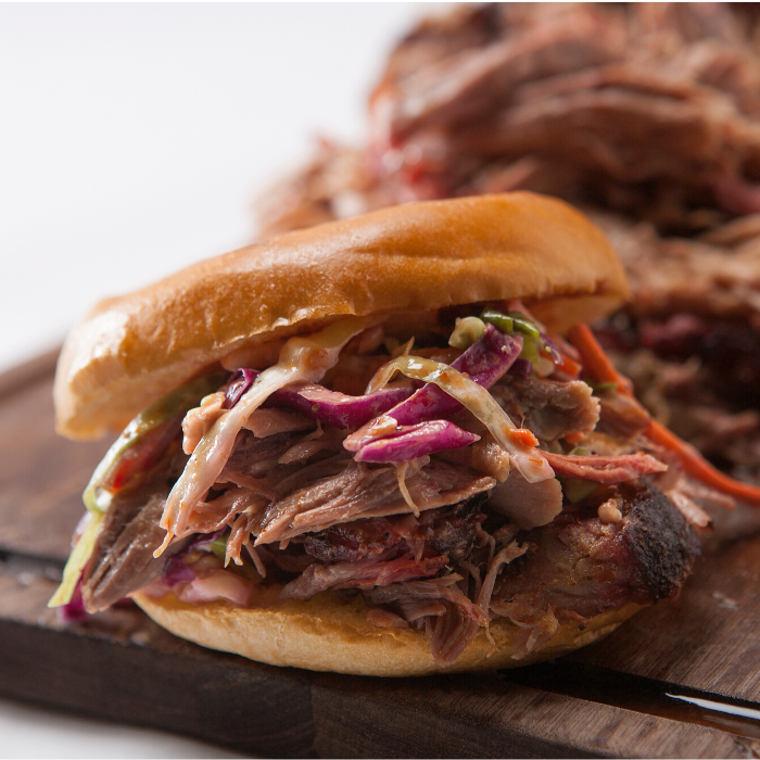 Brown sugar pulled pork and coleslaw sandwich in front of a pile of brown sugar pulled pork.