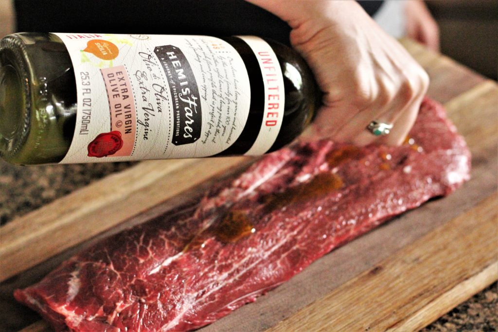 Raw, rectangular shaped flat iron steak on a wood cutting board. Hand is drizzling olive oil on steak from a green glass bottle