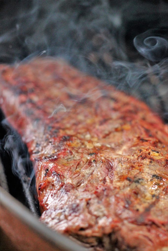 Slightly charred flat iron steak on grill grates with smoke swirling