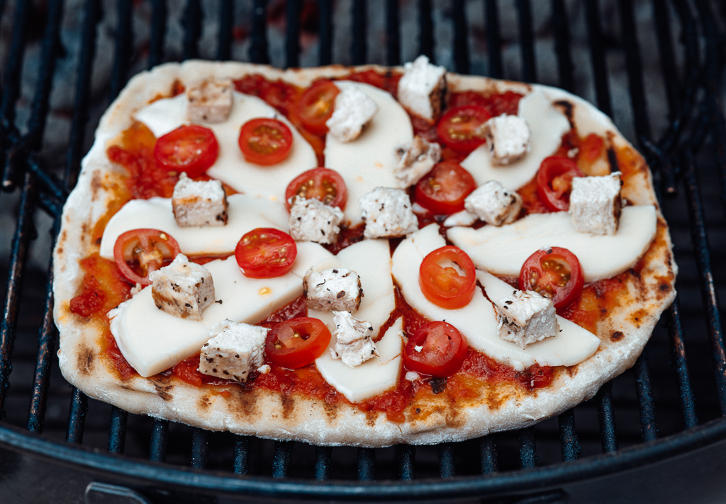 Homemade pizza being cooked on a charcoal grill.