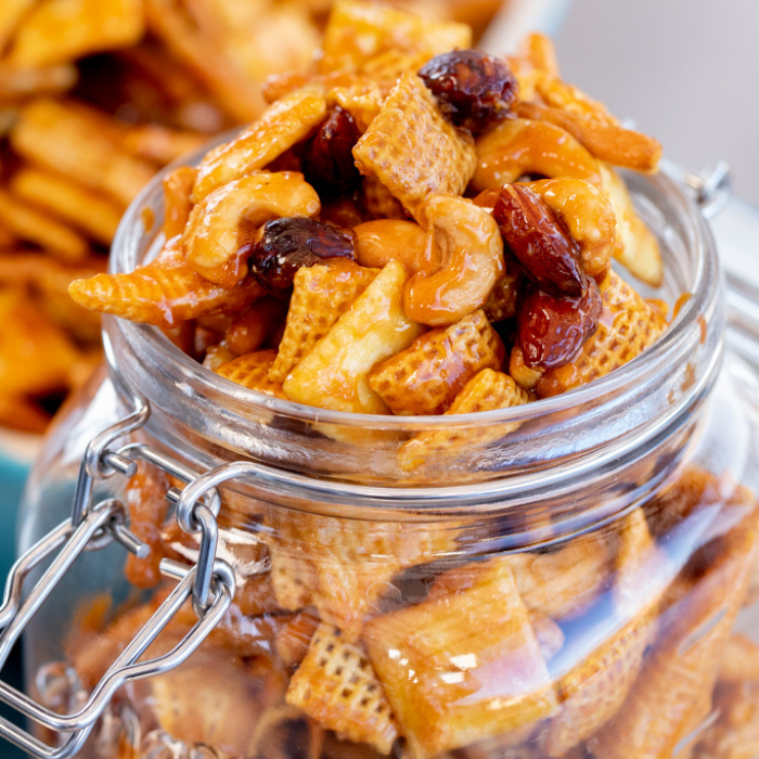 Smoked snack mix in a hinged glass mason jar with a baking dish of snack mix in the background.