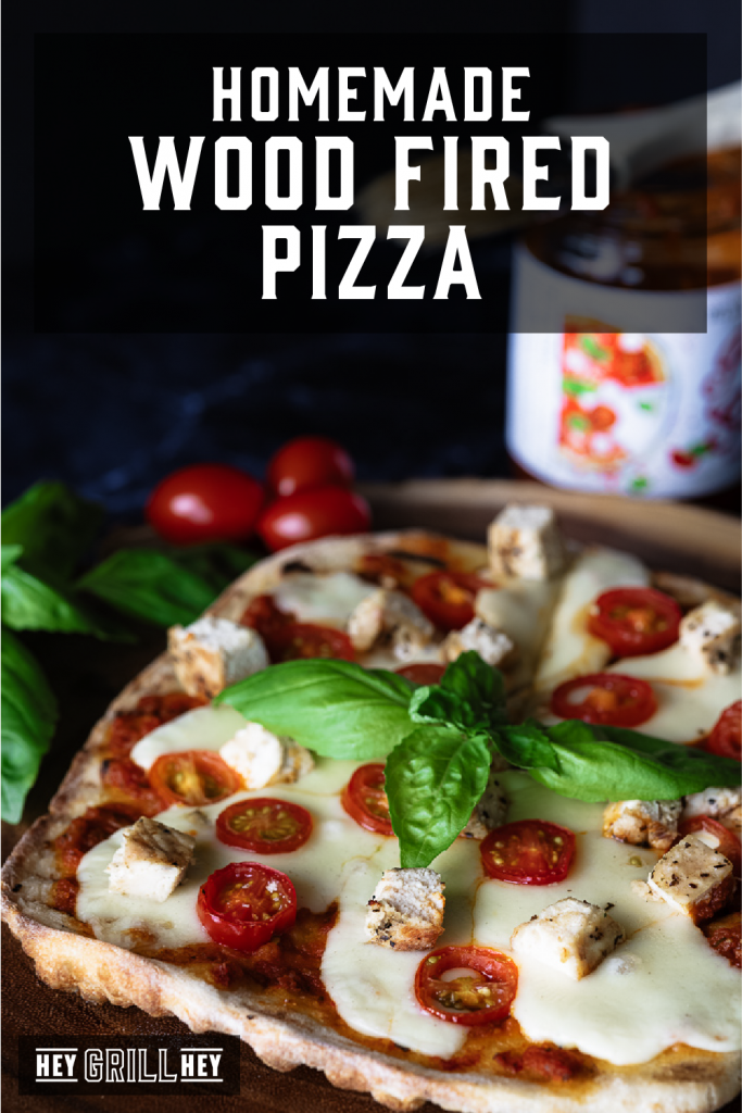 Wood Fired Pizza surrounded by fresh basil and cherry tomatoes with tomato sauce in the background and text overlay: Homemade Wood Fired Pizza.