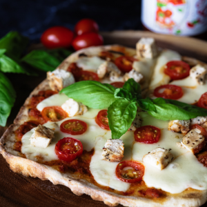 Wood Fired Pizza surrounded by fresh basil and cherry tomatoes with tomato sauce in the background.