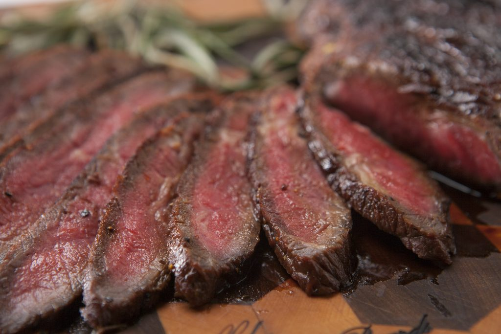 Grilled London broil sliced and arranged on a wood cutting board with fresh rosemary sprigs