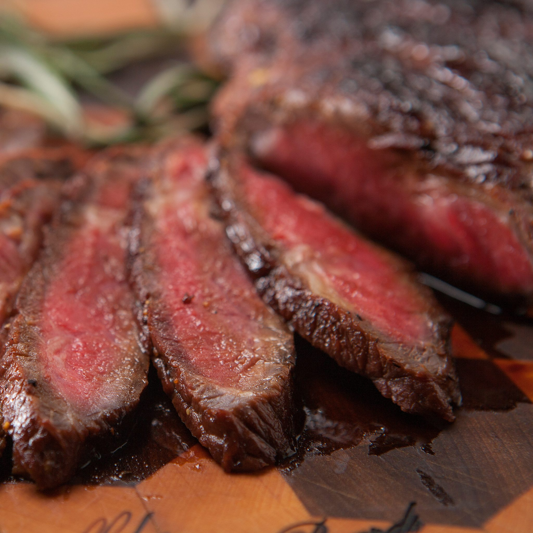Sliced marinated London broil fanned out on a wooden cutting board.