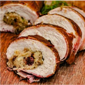 Bacon wrapped turkey breast roulade sliced and lined up on a wooden cutting board.