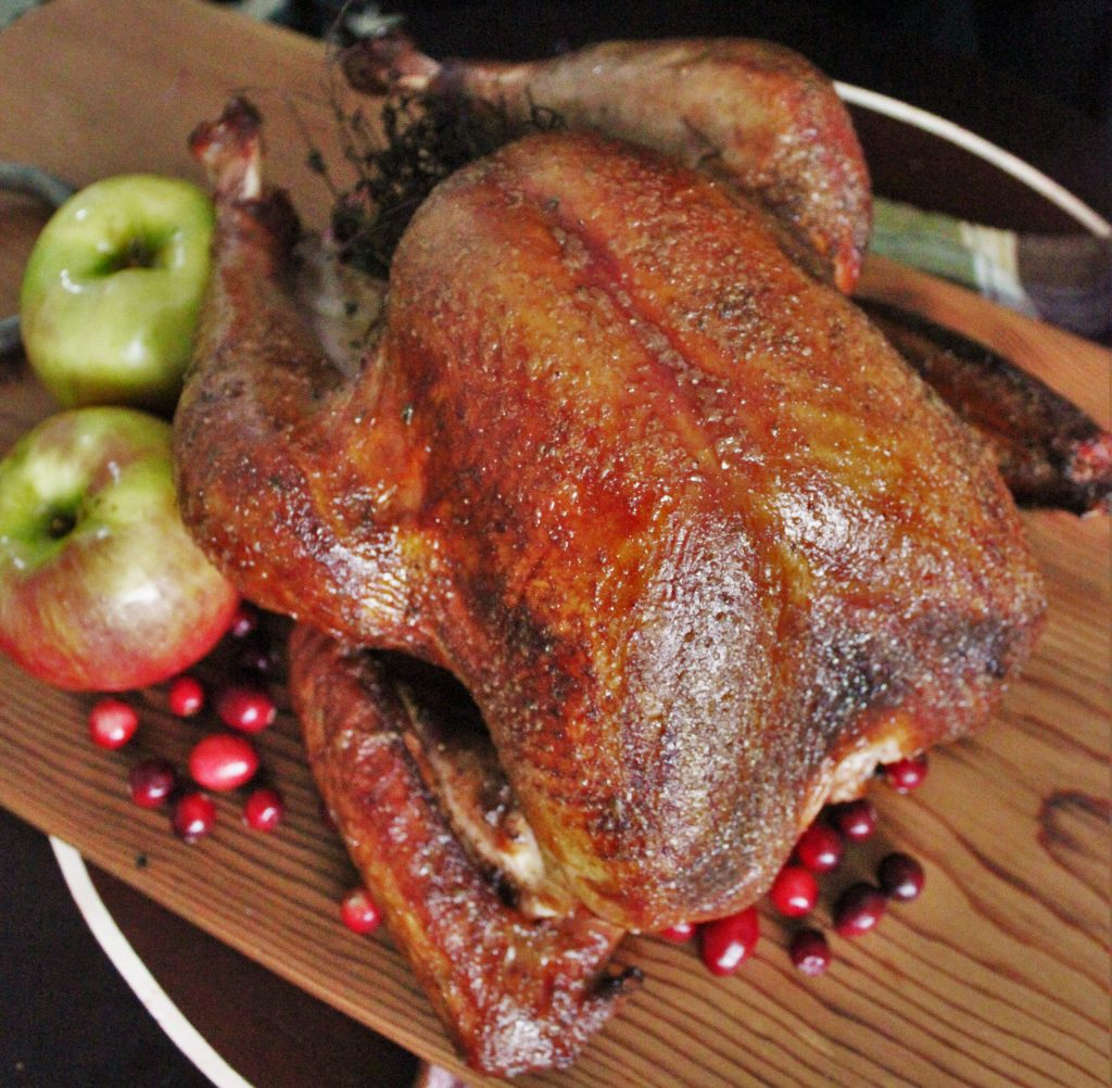 Smoked turkey on a wood cutting board with whole apples and cranberries.