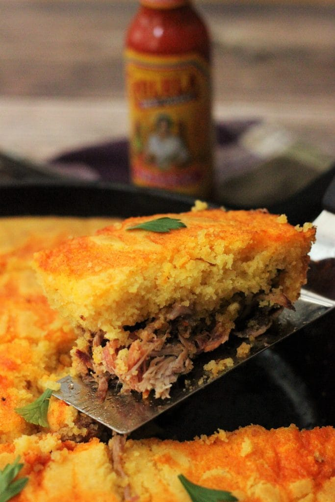 Close up shot of a portion Spicy Pulled Pork with Cholula Swirled Cornbread being lifted out of a cast iron skillet with a spatula.