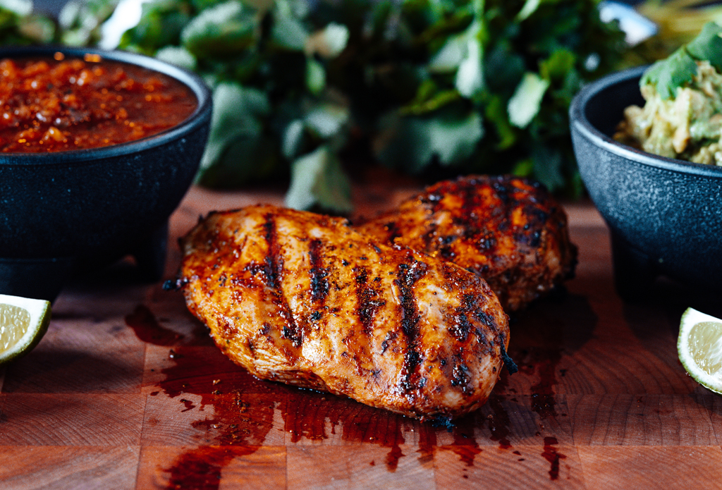 Two grilled chicken breasts on a wood cutting board between a bowl of salsa and a bowl of salad.