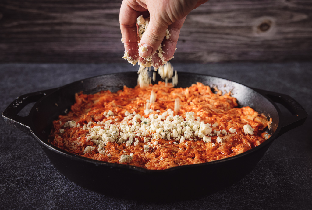 Blue cheese crumbles being sprinkled on top of smoked buffalo dip in a cast iron skillet.