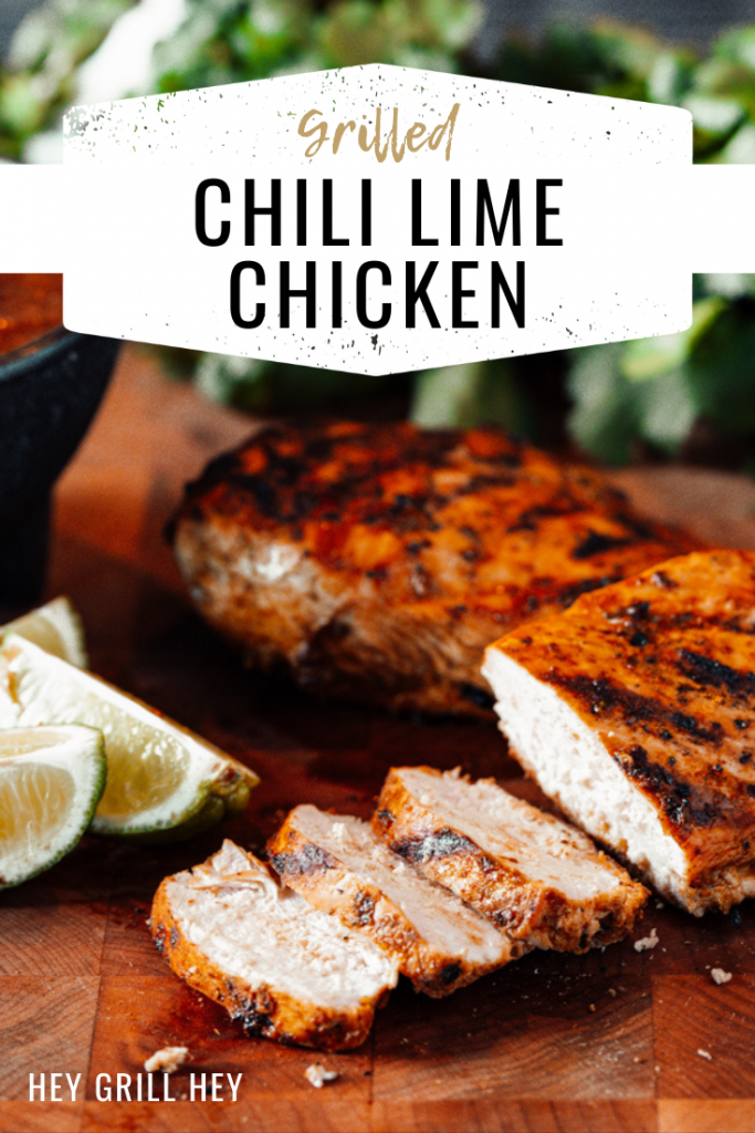 Sliced grilled chili lime chicken on a wooden cutting board with lime wedges and a whole grilled chicken breast in the background. Text overlay reads: Grilled Chili Lime Chicken.