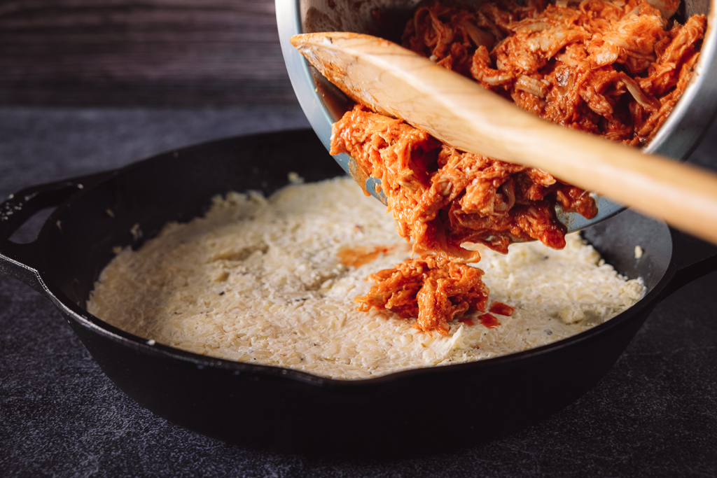 Buffalo chicken being spooned into a cheese sauce in a cast iron skillet.