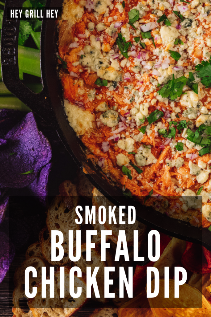 Buffalo chicken dip in a cast iron skillet surrounded by crostini and fresh veggies. Text overlay reads: Smoked Buffalo Chicken Dip.