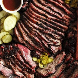 Smoked beef brisket sliced and garnished with pickles, a small bowl of BBQ sauce, and sliced peppers.