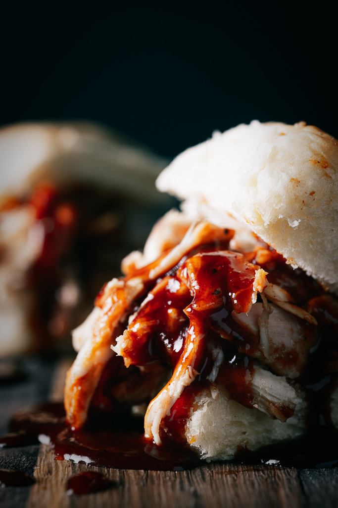 Smoked pulled chicken covered in whiskey peach BBQ sauce on a sandwich bun.