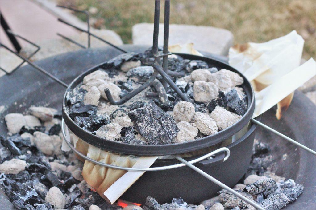 A dutch oven sitting in hot coals.