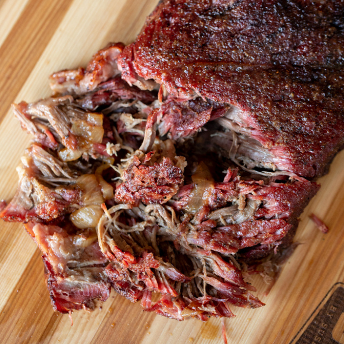 Shredded chuck roast on a wooden cutting board.