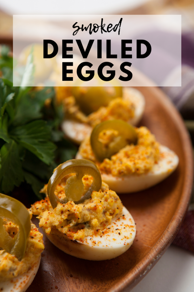 """Deviled eggs arranged in a circle on a wooden plate. Text overlay reads, """"Smoked Deviled Eggs."""""""