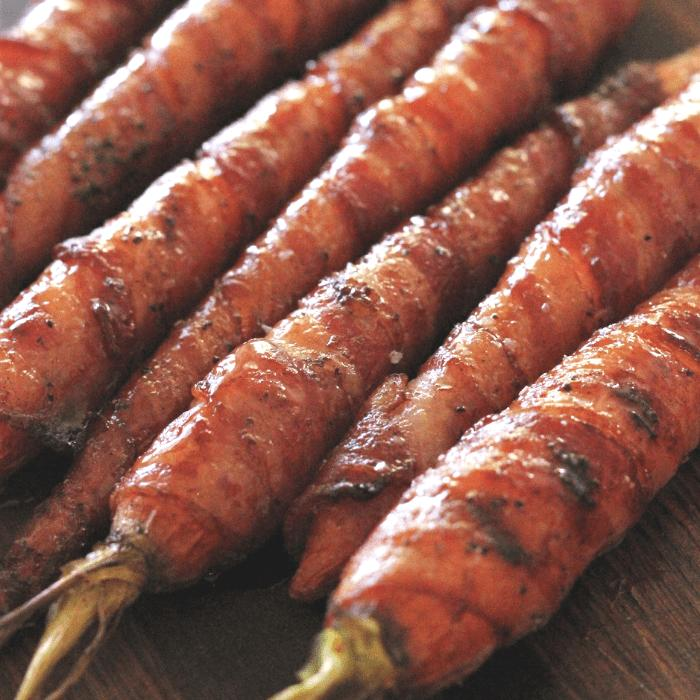 Bacon wrapped maple glazed carrots lined up on a wooden cutting board.