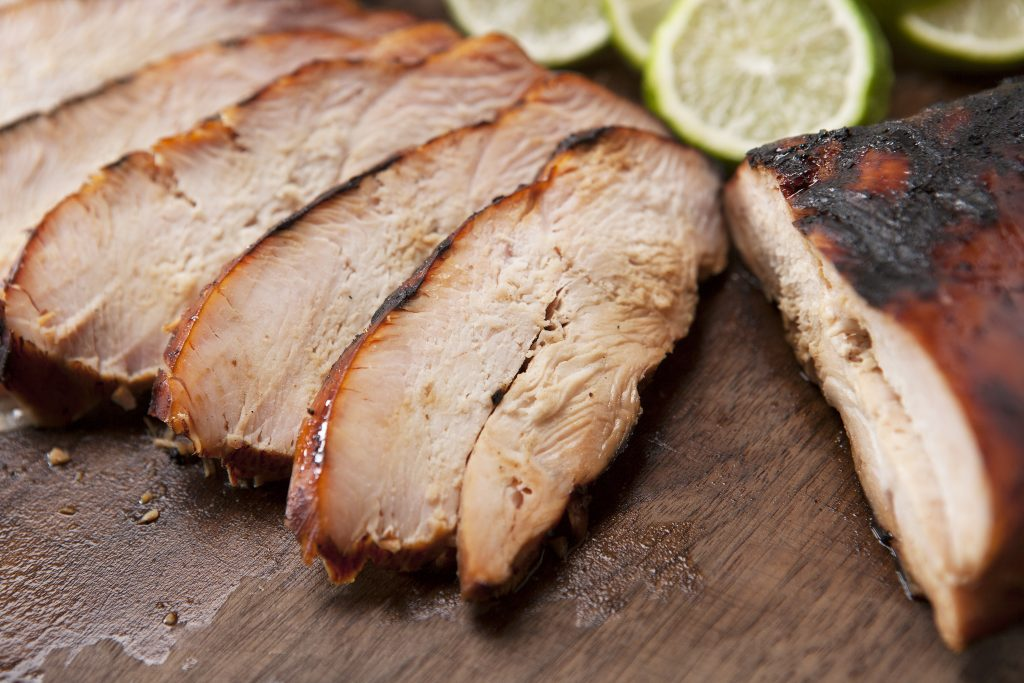 Sliced smoked turkey breast on a wood cutting board with sliced lemons and limes