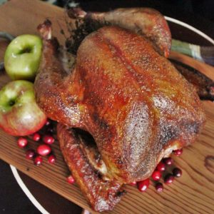 Whole smoked turkey on a wooden cutting board surrounded by fresh cranberries and whole apples.