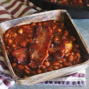 Smoked baked beans in a wooden bowl on top of a striped kitchen towel.