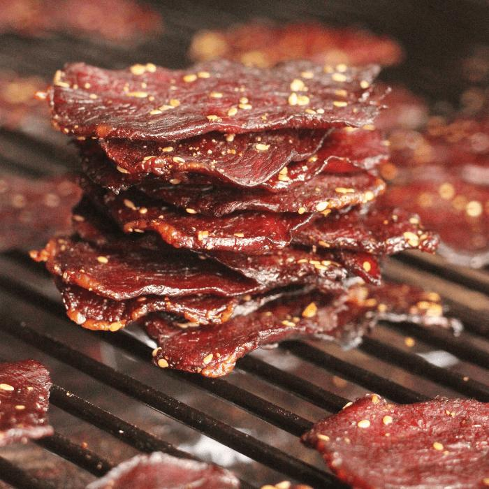 Stack of teriyaki beef jerky on the grill grates of a smoker.