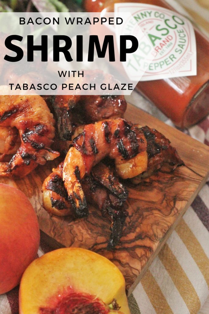 Bacon Wrapped Shrimp on a wooden board with a peach sliced in half and bottle of tabasco laying on it's side