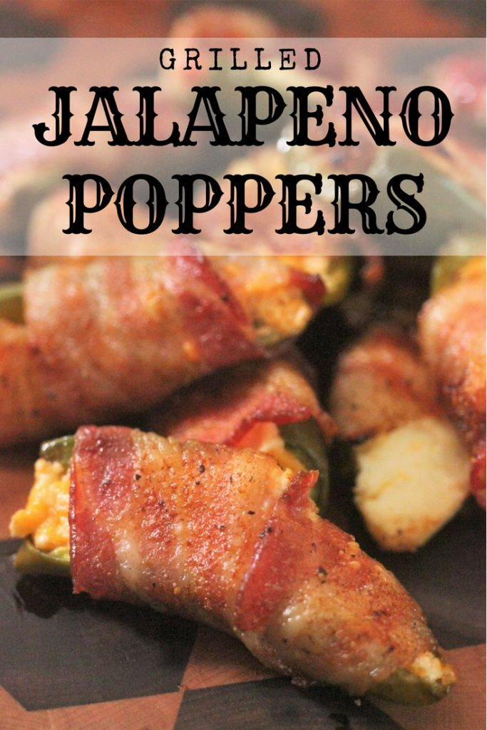 Grilled Jalapeno Poppers wrapped in bacon on a wood cutting board.
