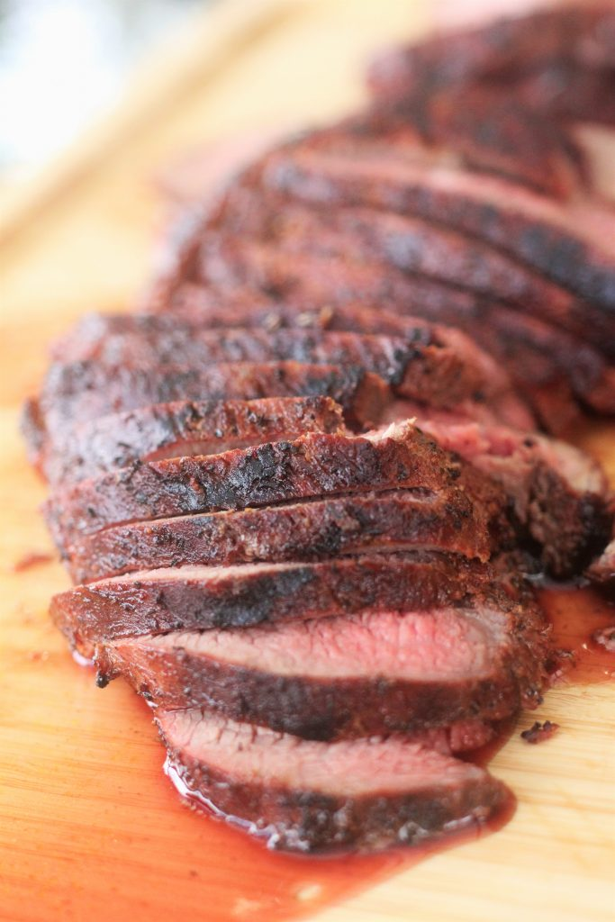 Seasoned and grilled steak sliced on a wood cutting board.