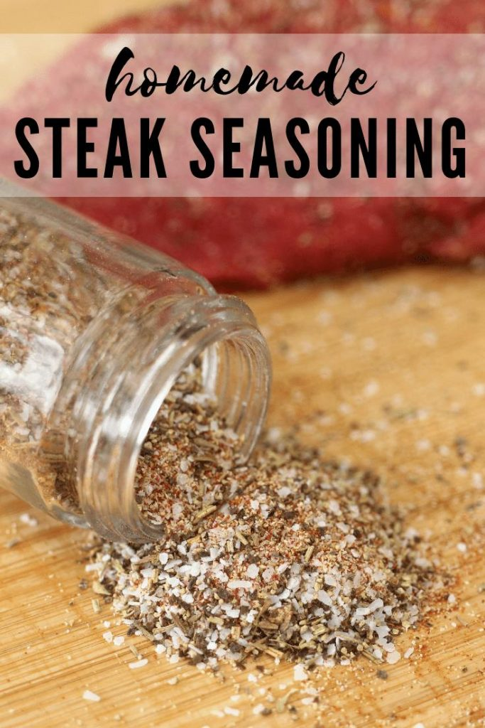 Homemade Steak Seasoning spilling out of a glass jar onto a wood cutting board.