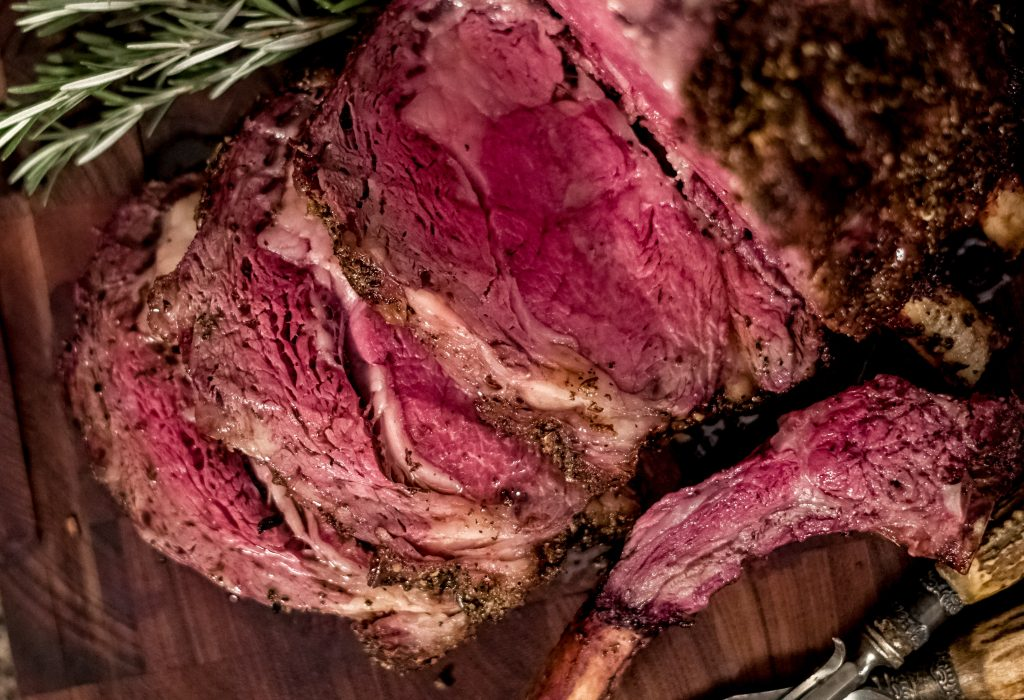 Finished and sliced medium rare Garlic Butter Smoked Prime Rib displayed on a wood cutting board. Overhead view.