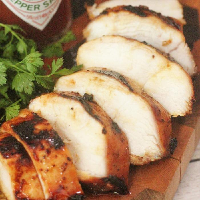 sliced sweet heat marinated grilled chicken breast on a wooden cutting board next to fresh herbs