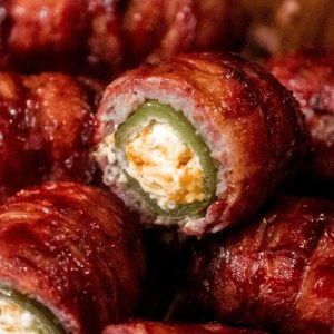 Close up of sliced and stacked bacon wrapped armadillo eggs.