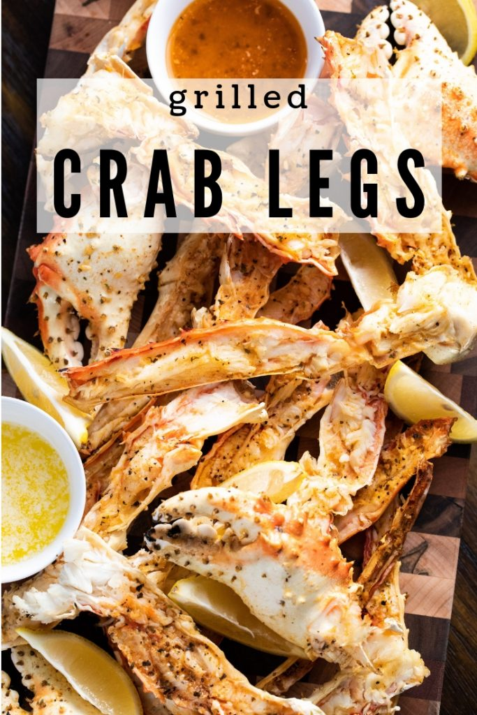 A pile of grilled crab legs cut in half on a wood cutting board next to bowls of dipping sauce.