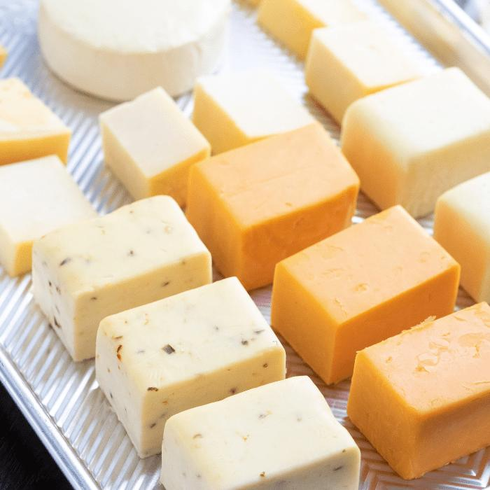 Cubes of smoked cheese on a metal baking dish.