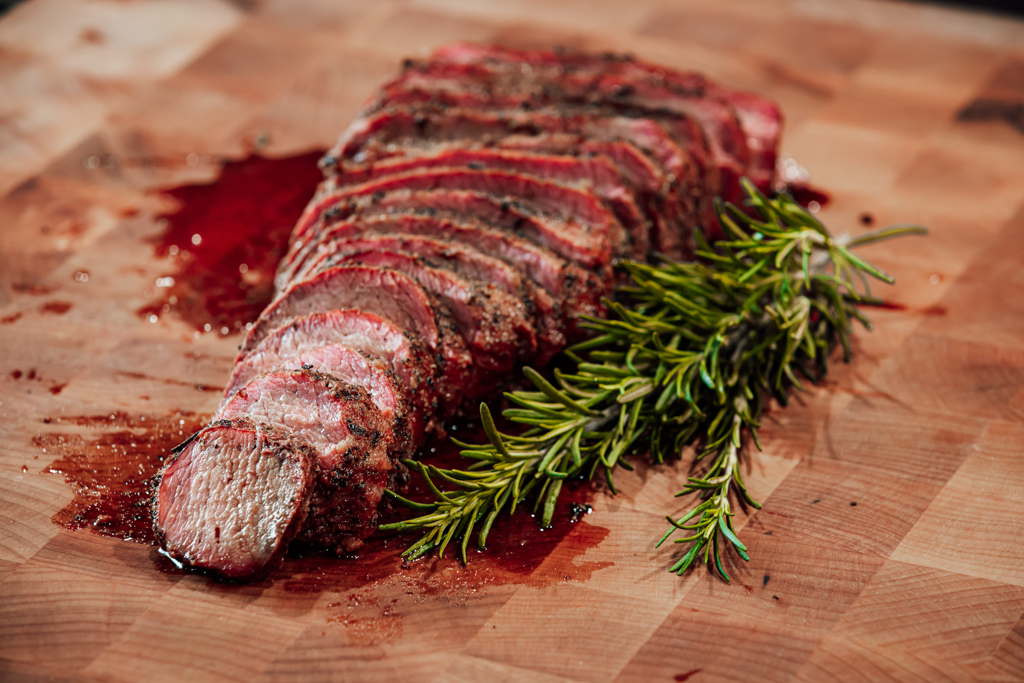 Sliced tri tip on a wooden cutting board next to sprigs of fresh rosemary.