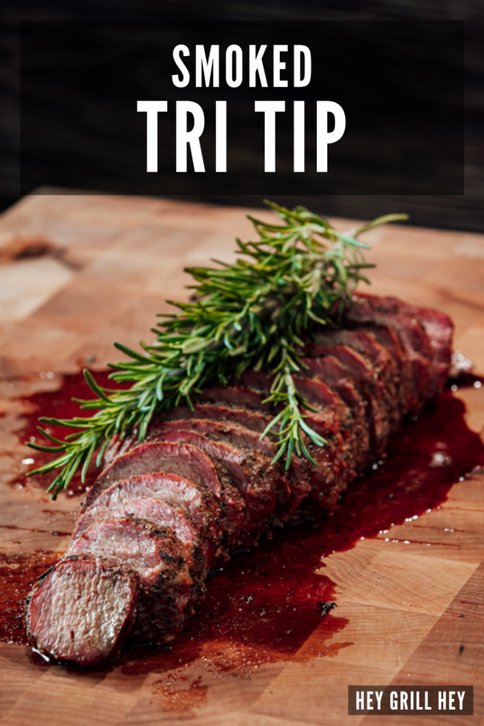 Sliced tri tip topped with fresh rosemary sprigs on a wooden cutting board. Text overlay reads: Smoked Tri Tip.