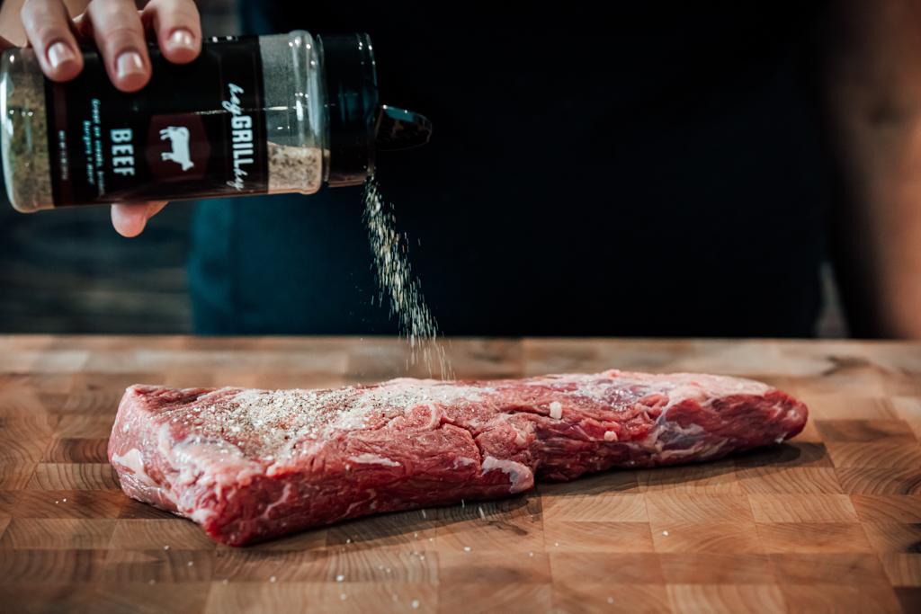Bottle of Hey Grill Hey Beef Seasoning sprinkling seasoning on an uncooked tri tip.