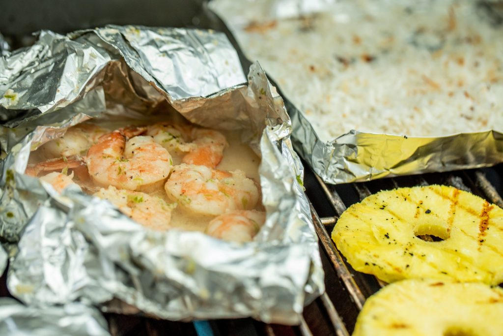shrimp in a foil packet, coconut in a foil packet, and pineapple slices on a grill.