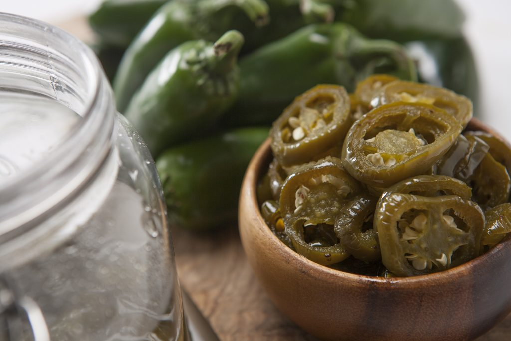 Candied jalapenos in a small wooden bowl in front of a small pile of fresh jalapenos