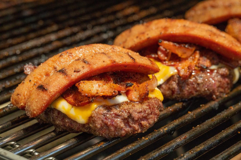 Hamburger patties topped with cheese, bacon, and hot dog on a grill grate.
