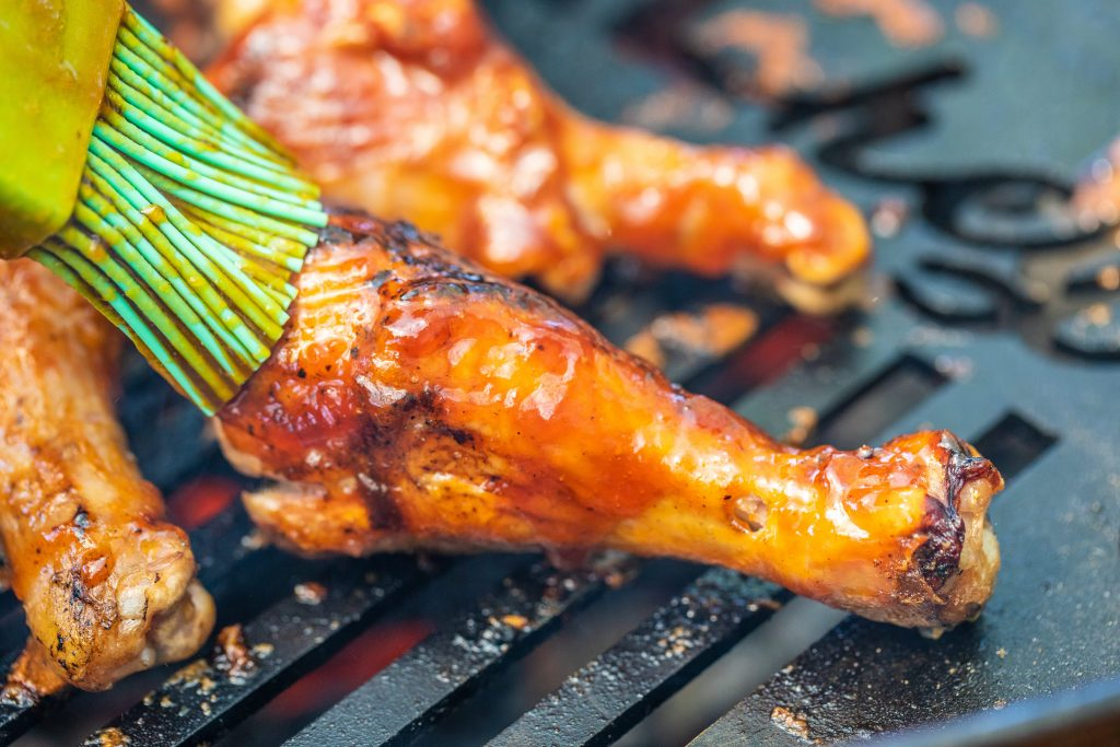 chicken drumsticks on a grill being basted with BBQ sauce by a basting brush.