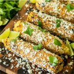 Mexican street corn on a wooden cutting board garnished with lime wedges and cilantro.