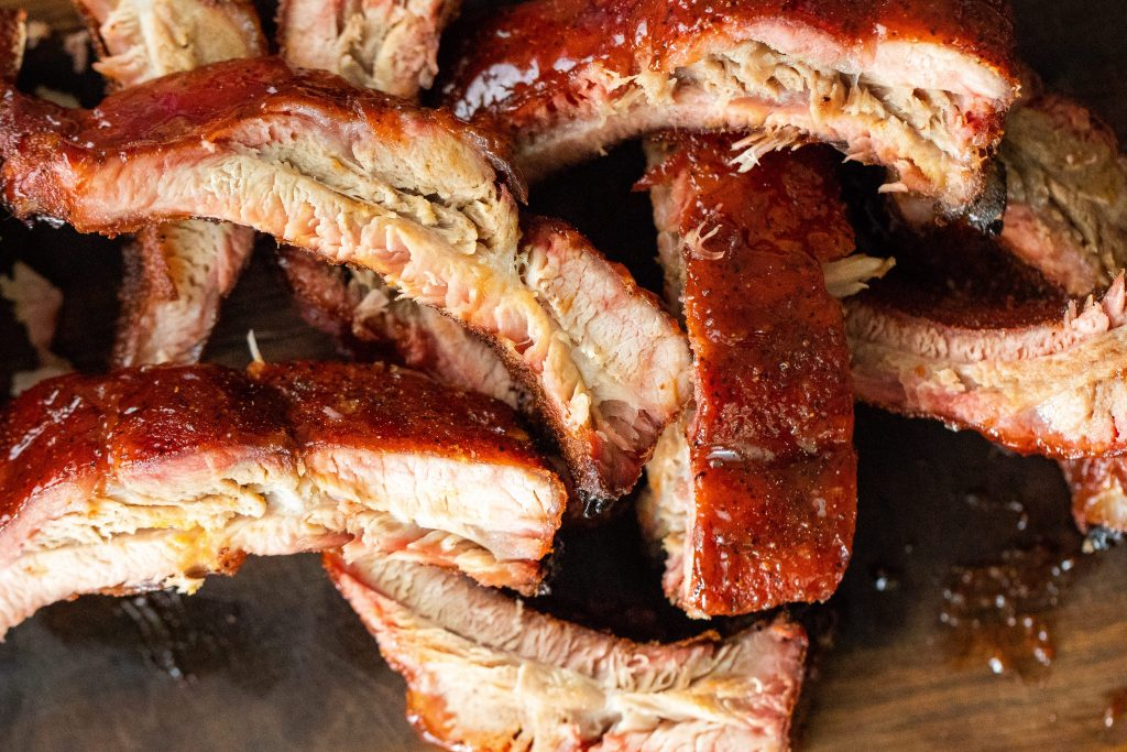 Overhead view of sliced smoked ribs, topped with maple bourbon glaze.