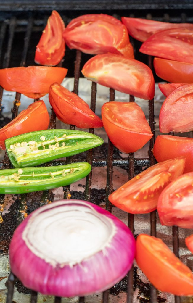 tomatoes, jalapenos, and a purple onion sliced and on the grill grates inside the grill.