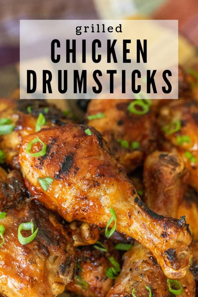 grilled chicken drumsticks with sliced green onions and BBQ sauce.